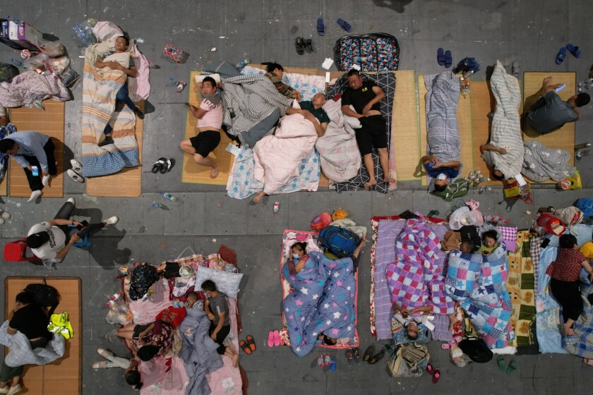 Migrant workers and their family rest in an exhibition hall after being evacuated from their workplaces in Hangzhou in eastern China's Zhejiang province Sunday, July 25, 2021. A typhoon blew heavy rain across the Shanghai region Monday, leaving roads and low-lying areas waterlogged and felling billboards and signs on its second landfall in eastern China. (Chinatopix via AP)