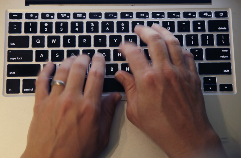 Fingers type on a computer keyboard.
