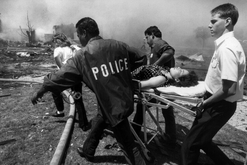 Aug. 31, 1986: A woman, who collapsed while watching rescue efforts in Cerritos, is wheeled from the scene.