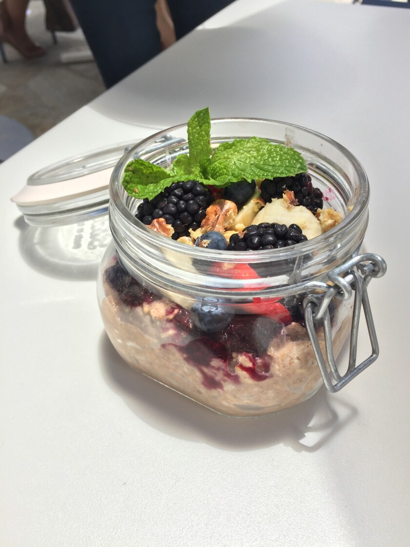A jar of chilled overnight oats and chia seeds with fresh fruit and house granola at Parakeet Cafe in La Jolla, Del Mar and Little Italy.