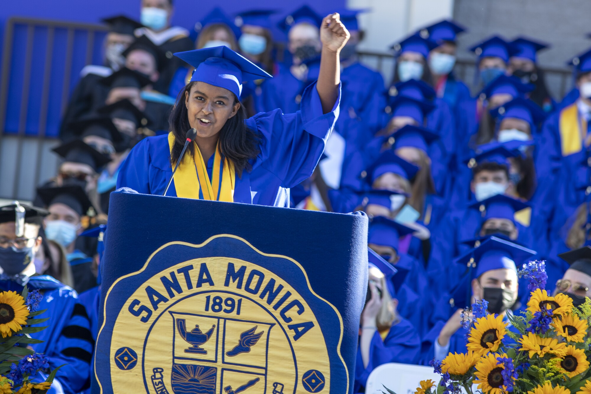 A high school graduate in cap and gown speaks into a microphone at a lectern and lifts one fist in the air.