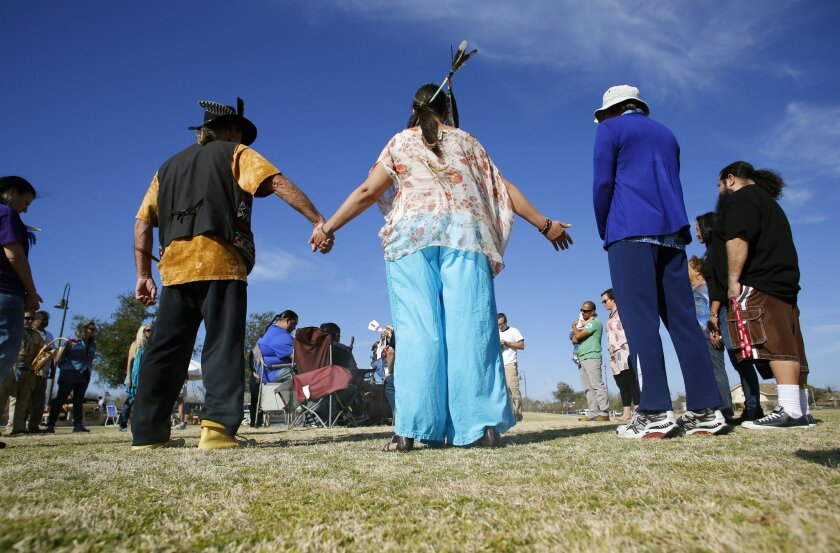 "Participants gather around the drum as members of several tribes preformed a rain dance on Saturday to attack the drought from a ""spiritual perspective."""