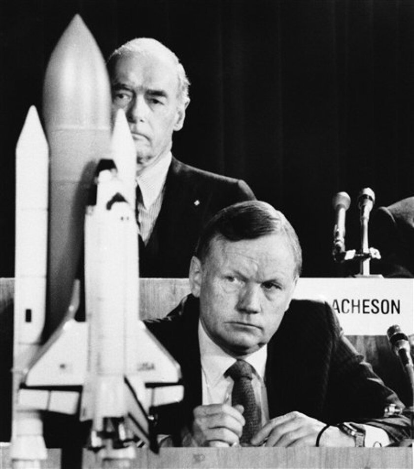 FILE - In this Feb. 11, 1986 file photo, former astronaut Neil Armstrong, a member of the presidential panel investigating the Space Shuttle Challenger explosion, listens to testimony before the commission in Washington, as David Acheson, a commission member, listens in the background. A model of t