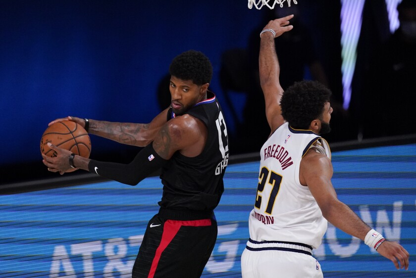 Clippers' Paul George grabs a rebound in front of Denver Nuggets' Jamal Murray.