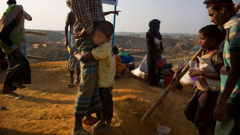 A Rohingya refugee boy clings to his father in the no-man's land between Myanmar and Bangladesh.