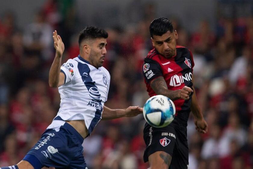 El jugador de Atlas Jefferson Duque (d) disputa el balón con Néstor Vidrio (i) de Puebla, durante el juego correspondiente a la jornada 6 del torneo mexicano de fútbol, celebrado en el estadio Jalisco, en la ciudad de Guadalajara (México). EFE