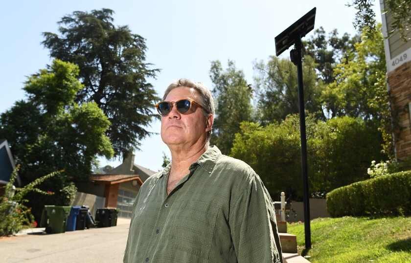 Robert Shontell stands along a street in Sherman Oaks where security cameras are installed to read license plates.