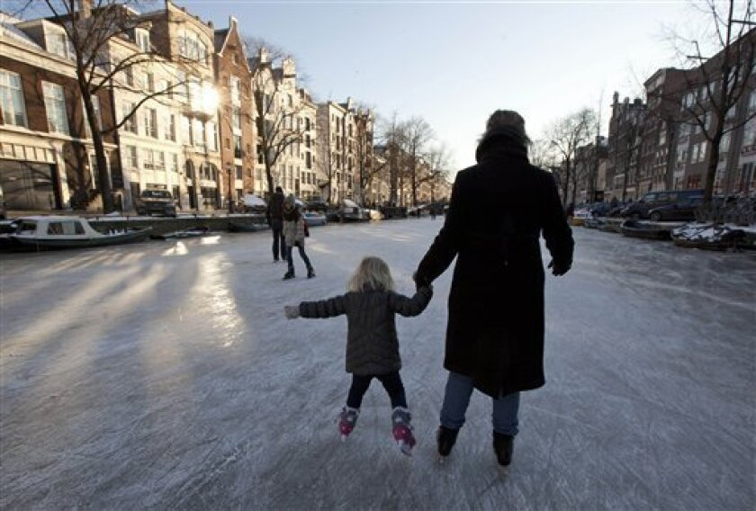 """Skaters enjoy a ride on frozen Prinsengracht canal in Amsterdam, Netherlands, Monday Feb. 6, 2012. While sports events across Europe fall victim to the deep freeze, the Dutch are welcoming the drop in temperatures, hoping that the revered """"Eleven Cities"""" speed skating race can be staged later this month for the first time in 15 years. (AP Photo/Peter Dejong)"""