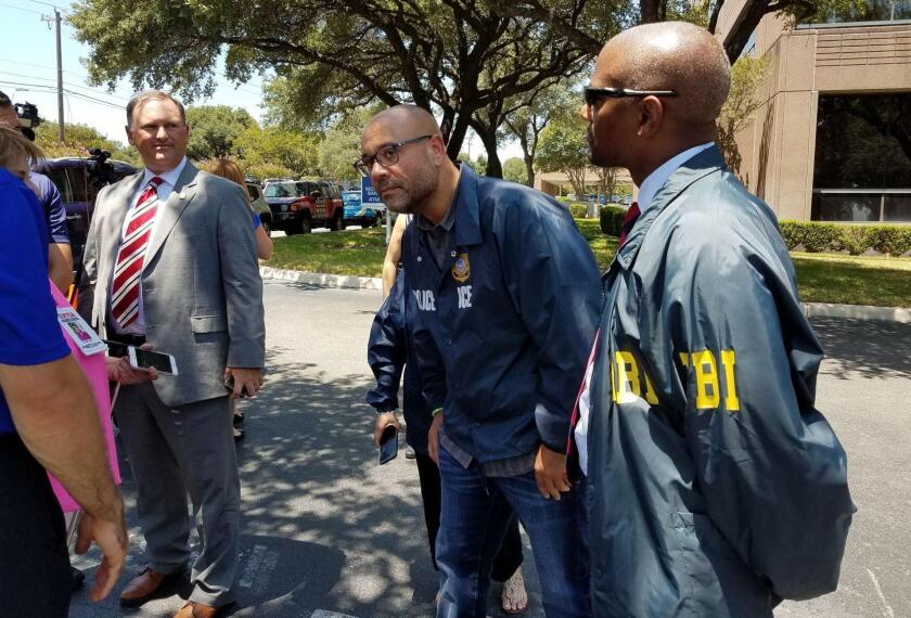 Agentes del FBI inspeccionan el lugar donde alguien disparó a dos edificios de San Antonio, Texas, donde trabajan empleados del Servicio de Control de Inmigración y Aduanas.