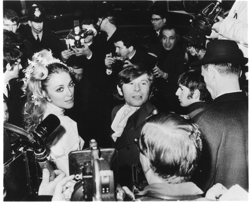 Sharon Tate and Roman Polanski, surrounded by men with cameras and a police officer, at their wedding in 1968.