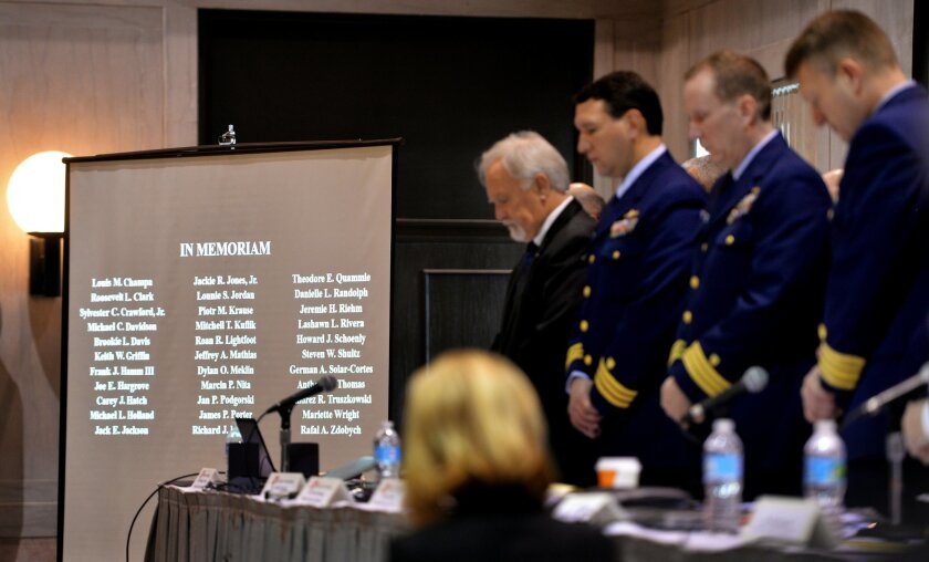 The investigative board stands during a moment of silence for the crew members lost during the sinking of the El Faro ship at the hearings in Jacksonville, Fla., Tuesday, Feb. 16, 2016.  The series of U.S. Coast Guard hearings will seek answers about why freighter El Faro sank near the Bahamas last