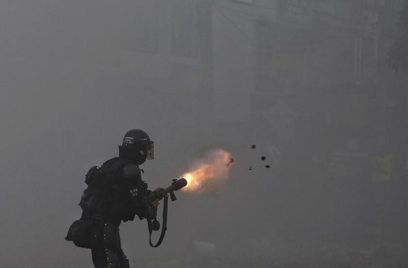 Un agente lanza gases lacrimógenos contra un grupo de manifestantes en Cali,