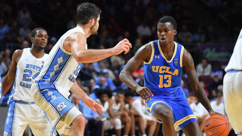 Kris Wilkes of UCLA dribbles against Luke Maye (32) of North Carolina.
