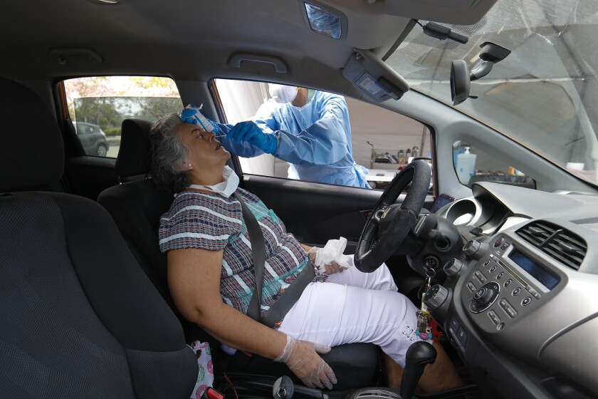 Sara Martinez, from Chula Vista, gets tested for COVID-19 in a drive-thru test site.