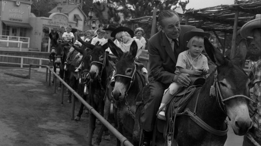 June 12, 1960: Walt Disney and his granddaughter Tammy Miller, 3, ride pack mules at opening of Disn