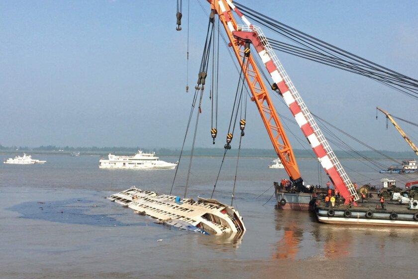 Cranes raise the sunken vessel Eastern Star in the Yangtze River in Jianli, central China's Hubei province.