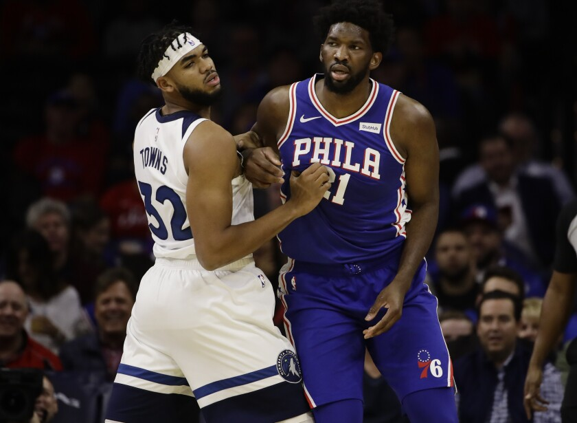 Minnesota's Karl-Anthony Towns and Philadelphia's Joel Embiid fight for post position during their game on Oct. 30, 2019.