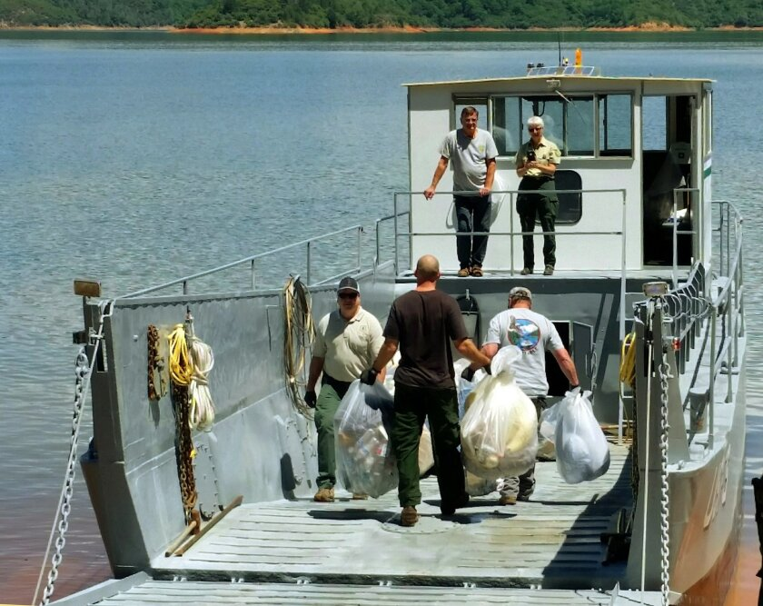 This Tuesday, May 24, 2016 photo provided by the U.S. Forest Service shows workers loading bags of trash on a boat after cleaning up a half-mile-wide swath of trash left behind by about 1,000 campers after an annual trip to Lake Shasta, Calif., by fraternity and sorority members. Shasta-Trinity Nat