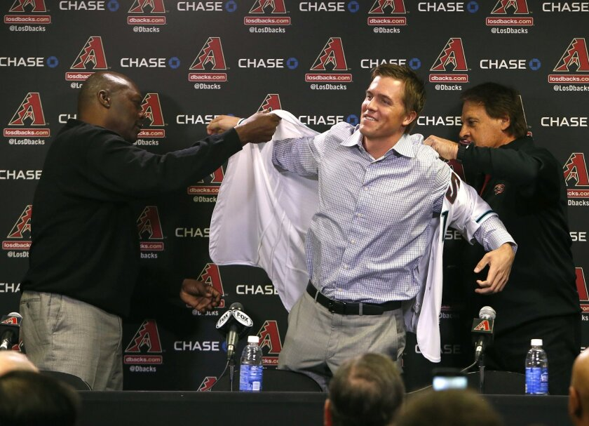 FILE - In this Dec. 11, 2015, file photo, Arizona Diamondbacks General Manager Dave Stewart, left, and Chief Baseball Officer Tony La Russa, right, introduce pitcher Zack Greinke to the media during a press conference, in Phoenix. Spring training is a time for optimism, when players bask under the