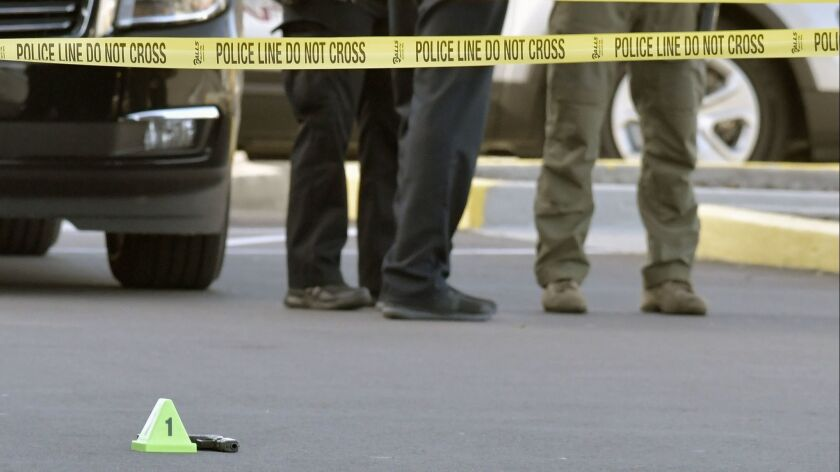 A gun lies on the ground inside a police barricade following a shooting at a Kroger grocery that lef