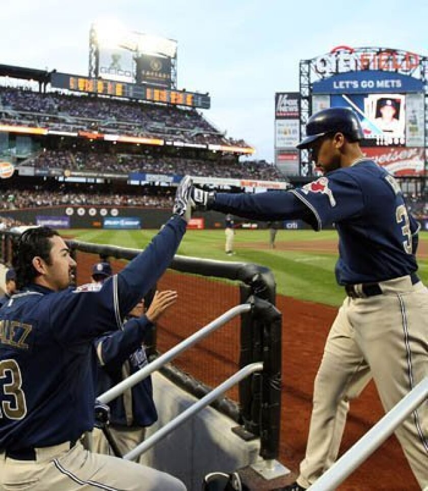 Jody Gerut celebrates with Padres teammate Adrian Gonzalez after Gerut hit a home run in the first at-bat of the game against the New York Mets during opening day at Citi Field on Monday.