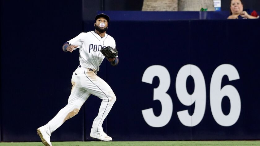 San Diego Padres center fielder Manuel Margot blows a bubblegum bubble on his way to making the catch of a fly ball hit by Colorado's Trevor Story during the sixth inning of a game Thursday, Sept. 21, 2017, in San Diego.