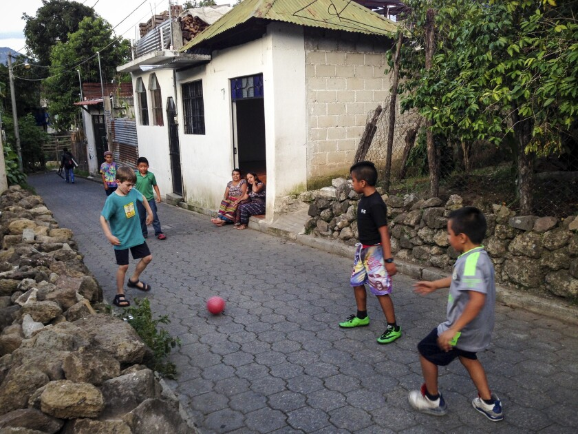 Liam Waring plays pick-up street soccer with neighborhood kids after a morning of Spanish lessons.