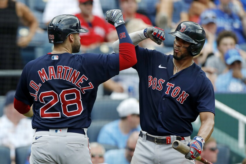 Boston Red Sox's J.D. Martinez (28) is congratulated by Xander Bogaerts (2) after hitting a two-run home run in the fifth inning of a baseball game against the Kansas City Royals at Kauffman Stadium in Kansas City, Mo., Saturday, June 19, 2021. (AP Photo/Colin E. Braley)