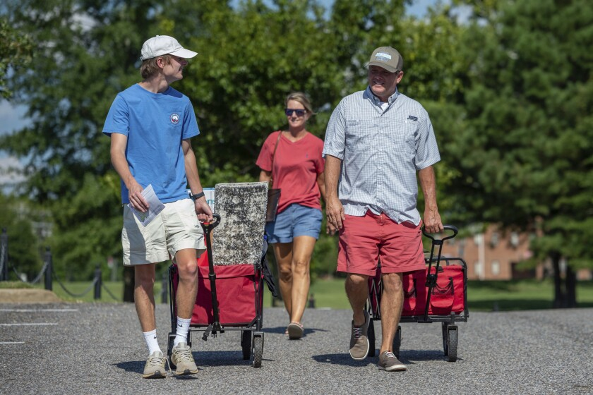 Baylor Garland, left, arrives to move in for his freshman year, assisted by his father Alan, right and mother, Teena, after they arrived from Eaton, Ga., at the University of Alabama on Saturday, Aug. 15, 2020, in Tuscaloosa, Ala. More than 20,000 students returned to campus for the first time since spring break with numerous school and city codes in effect to limit the spread of COVID-19. (AP Photo/Vasha Hunt)
