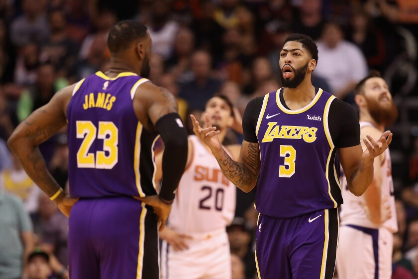 Lakers forward Anthony Davis, left, speaks with teammate LeBron James during a win over the Phoenix Suns earlier this month.
