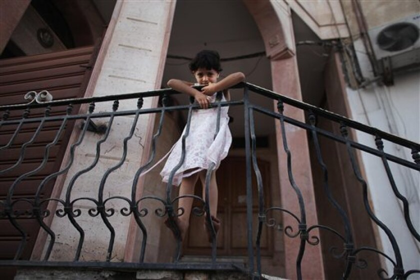 """A Libyan girl hangs onto a stairwell banister in downtown Tripoli, Libya, Tuesday, July 5, 2011. The U.S. Senate scheduled a vote on Tuesday whether to proceed with a resolution authorizing """"the limited use of United States Armed Forces in support of the NATO mission in Libya."""" The resolution would expire when the NATO operation ends or after one year, and it would prohibit the use of American ground forces or private security contractors in Libya. (AP Photo/Tara Todras-Whitehill)"""
