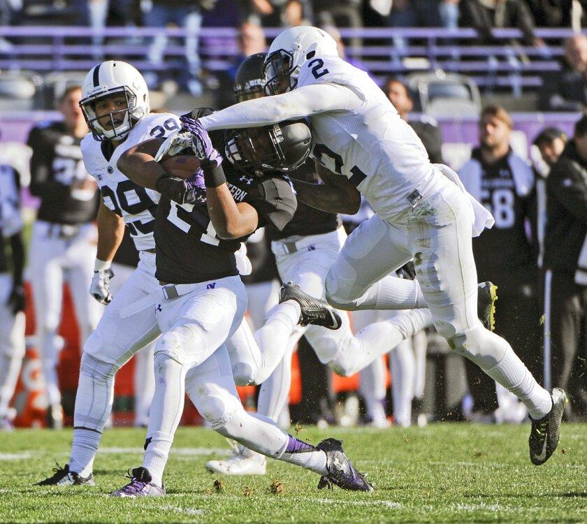 Northwestern running back Justin Jackson (21) runs against Penn State safety Marcus Allen (2) and cornerback John Reid (29)  during the second half of an NCAA college football game in Evanston, Ill.,  Saturday, Nov. 7, 2015. (AP Photo/Matt Marton)