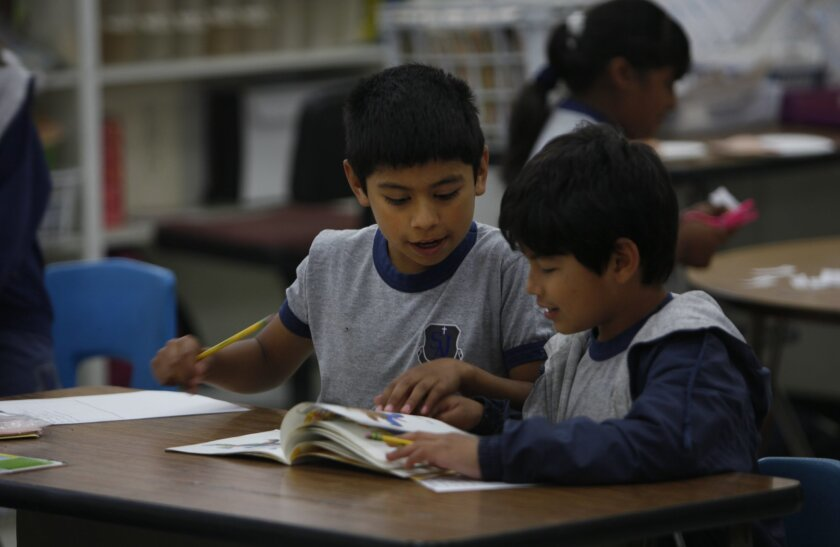Noel Gomez, 7, left, and Danny Barrigan, 7, read a book together in their second grade class at St. Jude Academy Thursday.