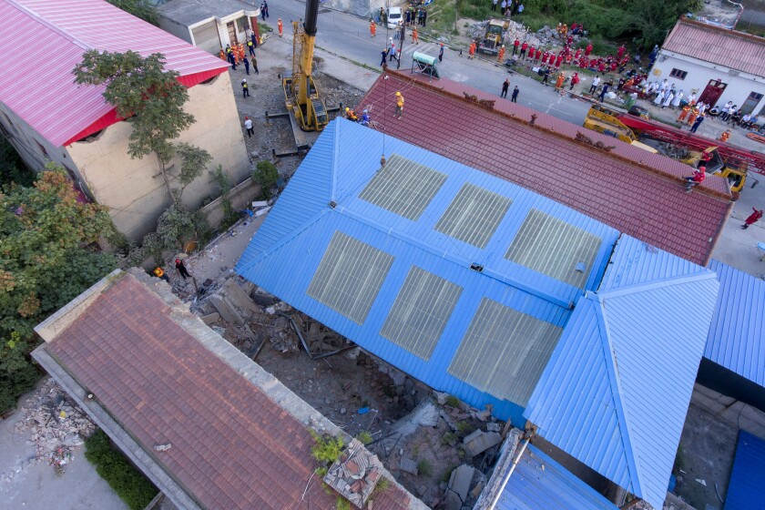 Rescuers work at the site of a collapsed two-story restaurant in a northern Chinese village.