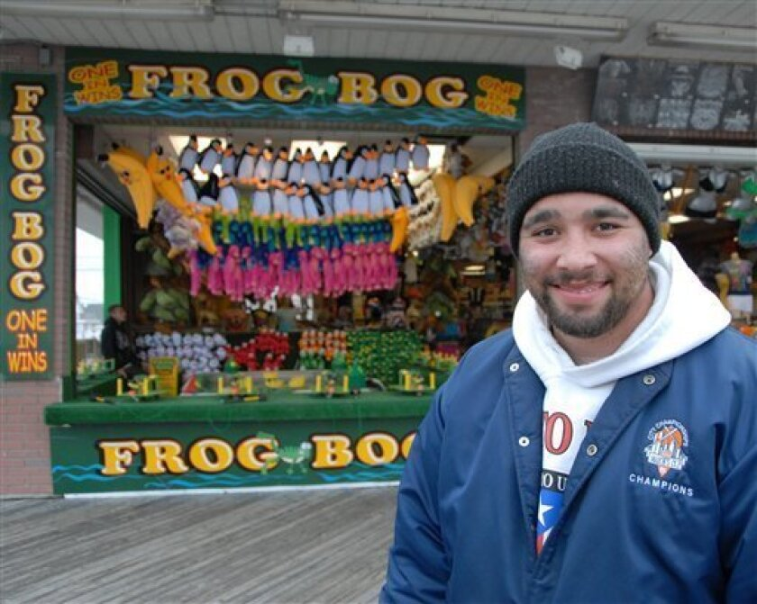 Ramon Villanueva in front of the Frog Bog arcade stand on the boardwalk in Seaside Heights, N.J. on Thursday, April 30, 2009. Villanueva was let go from his job as a corporate audio-video tech last October, had worked odd jobs, and recently was hired to run the game on the boardwalk. (AP Photo/Curt Hudson)