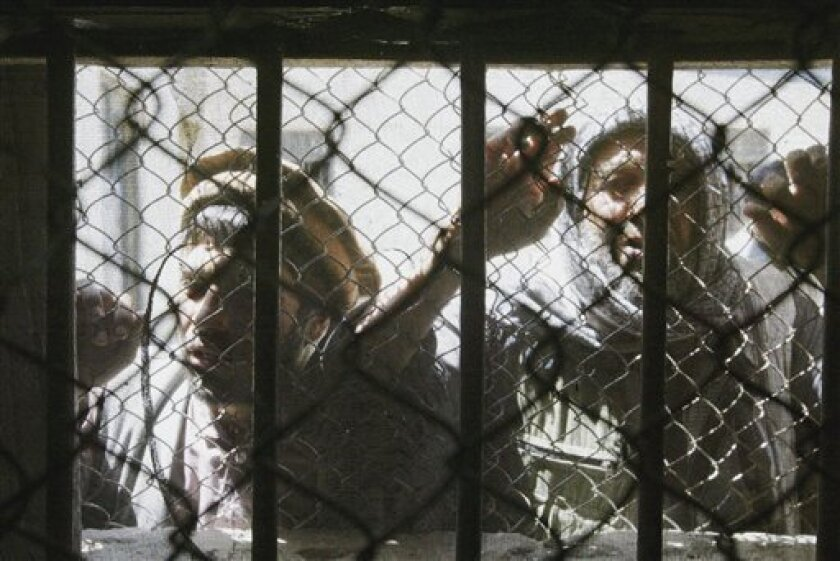 FILE-- In this file photo dated Friday, May 9, 2003, Afghan prisoners look out through a window at the Kabul's Prison in Afghanistan. Prisoners in some Afghan-run detention facilities have been beaten and tortured, a United Nations report said Monday Oct 10, 2011, but the international organization said that the mistreatment was not the result of government policy. (AP Photo/Silvia Izquierdo-FILE)