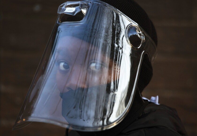 A student, wearing a face mask and shield, returns to school in Johannesburg, South Africa.
