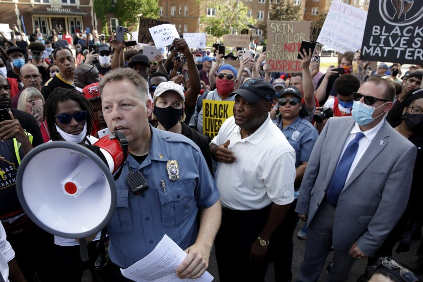 Kansas City Police Chief Rick Smith uses a megaphone to address protesters
