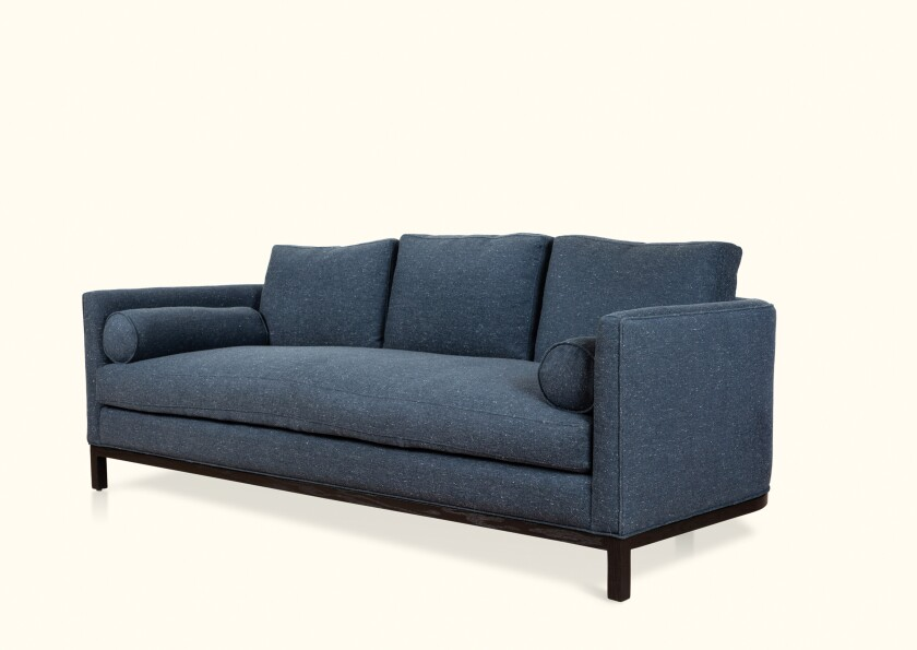 The Curved Back sofa from Lawson-Fenning features a single down-wrapped cushion with a trio of removable back cushions.