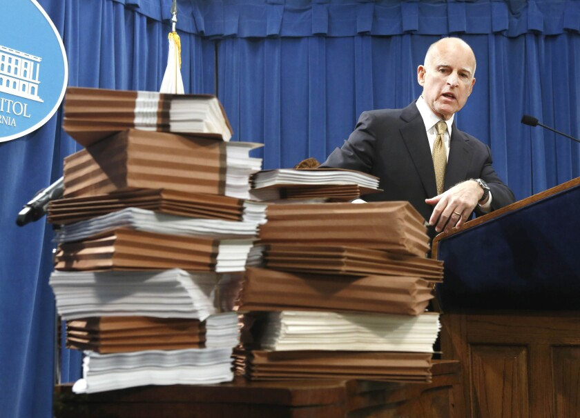 Gov. Jerry Brown gestures to a stack of reports on California prisons as he discusses his call for federal judges to return control of California prison to the state.