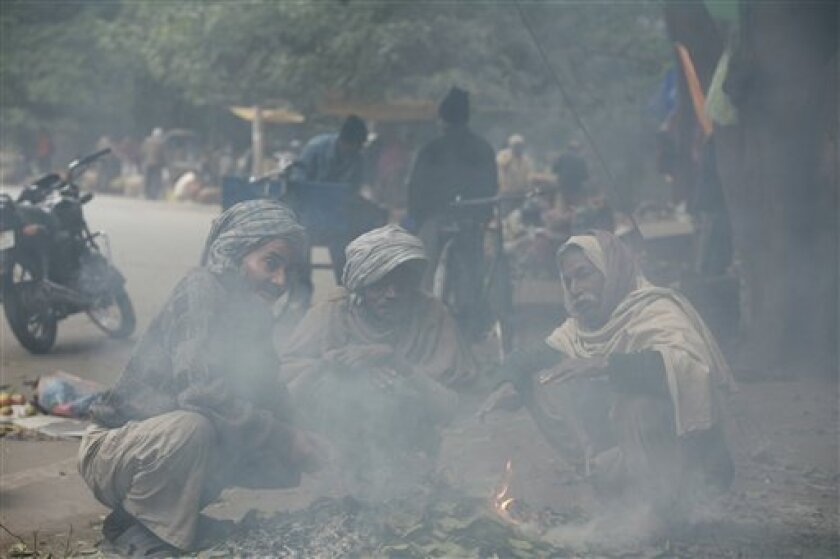 Indian labors warm themselves around a bonfire, on a cold and foggy morning in Allahabad, India, Sunday, Jan. 3, 2010. Four trains collided Saturday in two separate accidents caused by dense winter fog in northern India. The fog has also disrupted rail and road services. (AP Photo/Rajesh Kumar Singh)