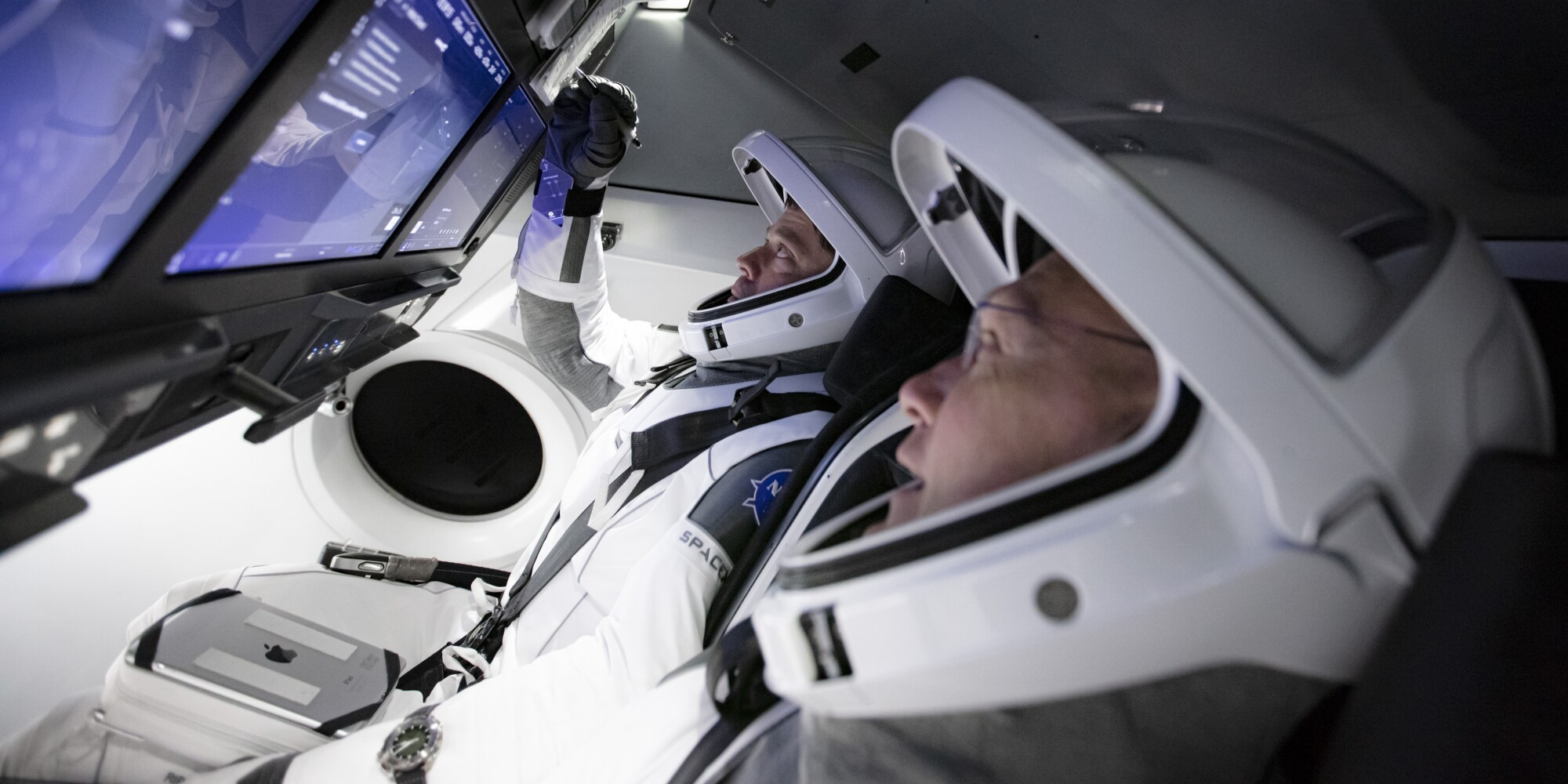 Astronauts Doug Hurley, foreground, and Bob Behnken work in SpaceX's flight simulator at the Kennedy Space Center in Cape Canaveral, Fla., in March.
