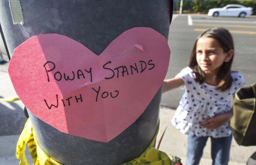 A young girl places a heart shape note, similar the one in the foreground, on a light pole near Chabad of Poway, where a man with a gun shot multiple people inside the synagogue, killing one, in Poway on Saturday, April 27, 2019 in Poway, California.
