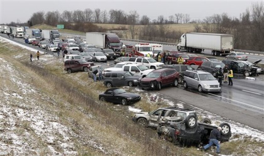 Emergency crews work the scene after a crash along Interstate 75 that involved about 30 cars during snowy conditions Monday, Jan. 2, 2012 near Dry Ridge, Ky. No life-threatening injuries were reported. The road reopened around 3 p.m. on Monday after being shut down for about three hours from the pileup. (AP Photo/The Cincinnati Enquirer, Patrick Reddy) MANDATORY CREDIT; NO SALES