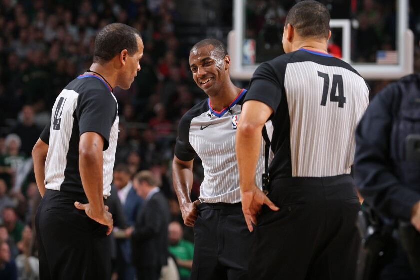 John Butler, center, who attended San Diego High, is in his first season as a full-time official in the NBA.