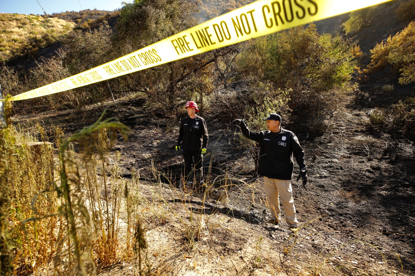 Los Angeles CA. JUNE 10, 2020 - LAFD Arson investigators Robert Williams, left, and Joe Sanchez investigate the origin of the brush fire that broke out after midnight in the Sepulveda Pass threatening homes of Bel Air Wednesday, June 10, 2020. Firefighters were able to stop forward movement of the blaze at about 50 acres. (Al Seib / Los Angeles Times)