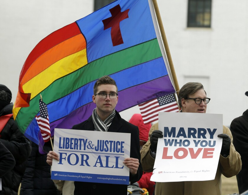 In this Feb. file photo, Spencer Geiger, left, of Virginia Beach, and Carl Johanson, of Norfolk, hold signs as they demonstrate outside Federal Court in Norfolk, Va. A new poll shows that acceptance is growing for same-sex marriage.