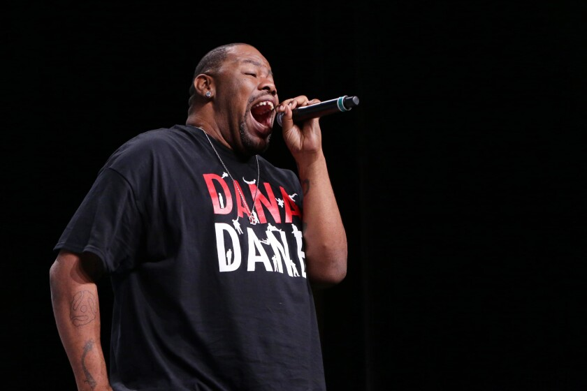 Biz Markie, on stage, holds a microphone.