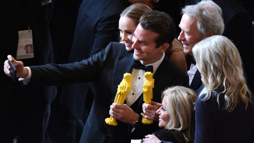 Model Suki Waterhouse, left, actor Bradley Cooper and director Clint Eastwood pause for a selfie with Oscars made of Legos at the Academy Awards in February.