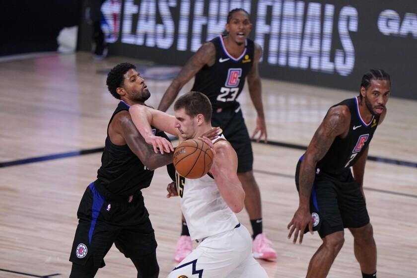 Denver Nuggets center Nikola Jokic drives against Clippers guard Paul George.